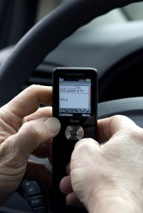 Driver texting with hands in front of steering wheel